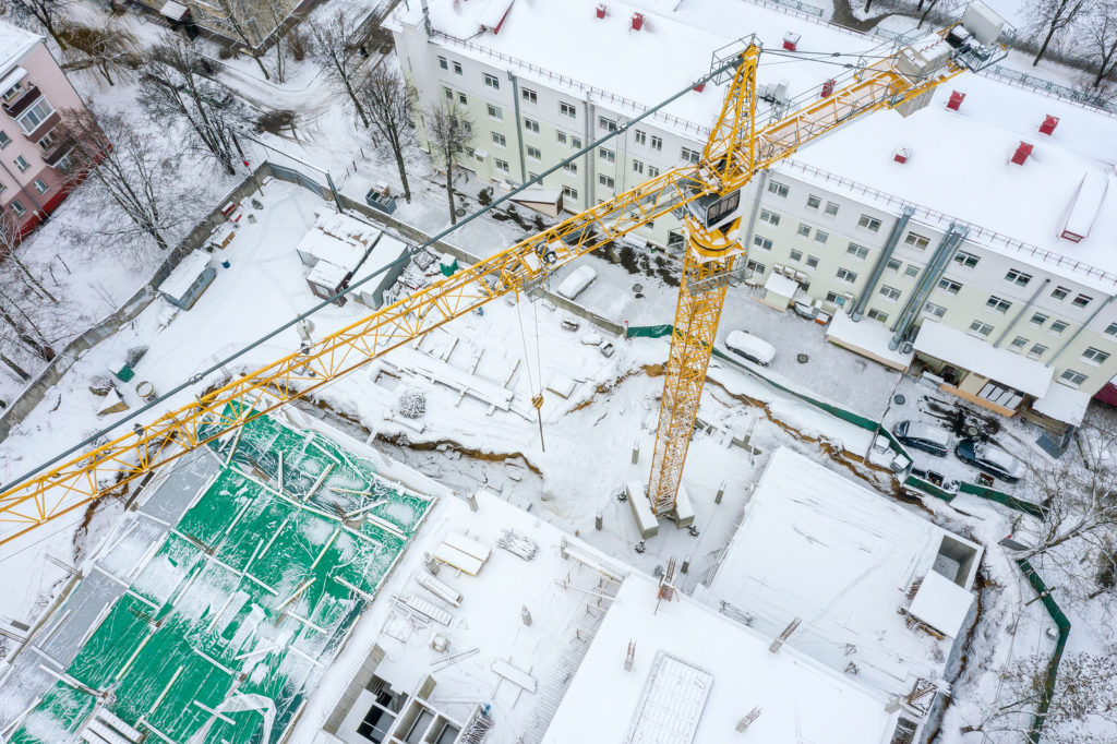 Aerial Top View Of Tall Tower Crane Working At Construction Site